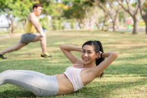 Pretty young girl doing crunches in the city park