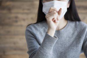 咳をするマスクをつけた女性